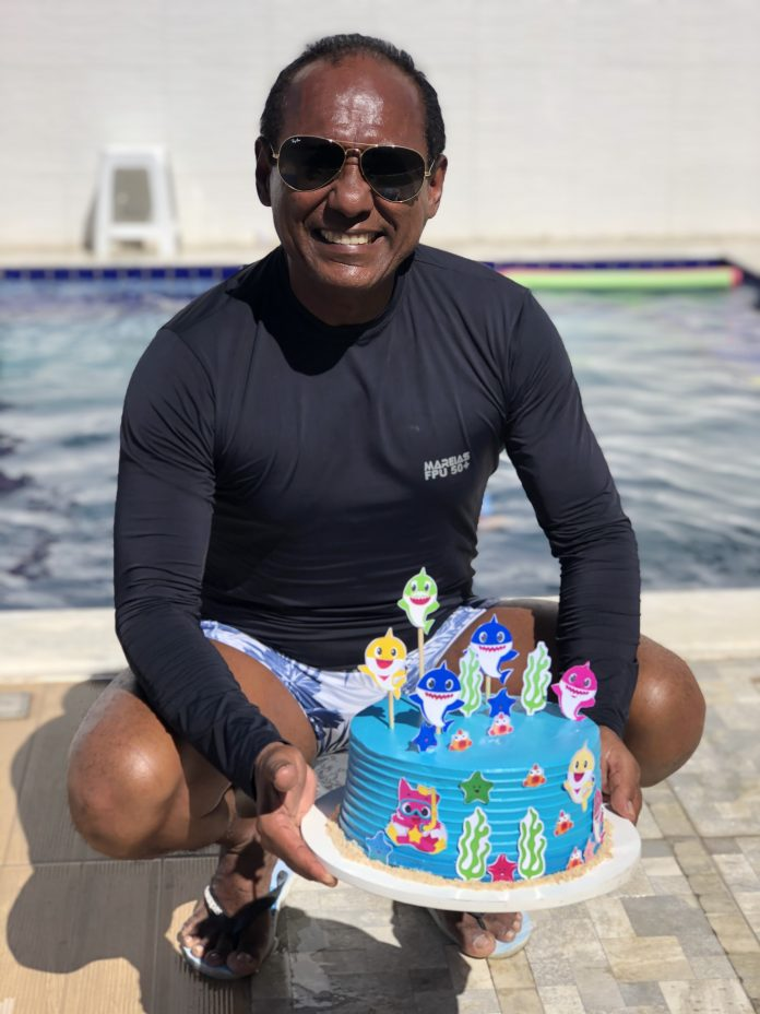 homem que faz festa na piscina em casa pafra as crianças segurando bolo